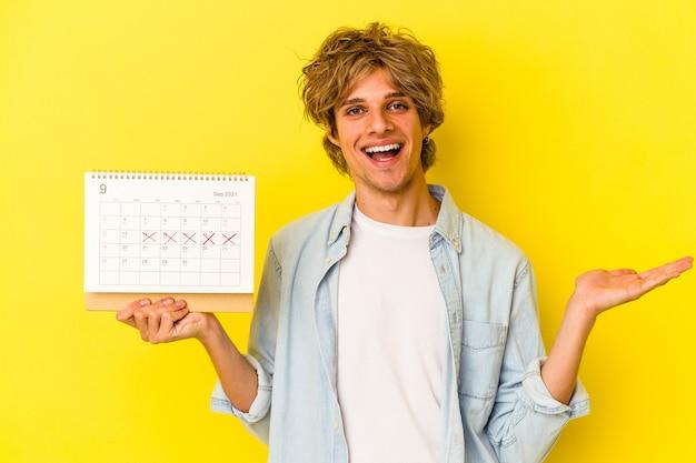 Jeune homme de race blanche avec du maquillage tenant un calendrier isolé sur fond jaune montrant un espace de copie sur une paume et tenant une autre main sur la taille.
