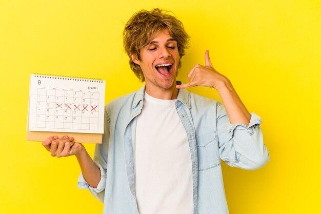 Jeune homme de race blanche avec du maquillage tenant un calendrier isolé sur fond jaune montrant un geste d'appel de téléphone portable avec les doigts.