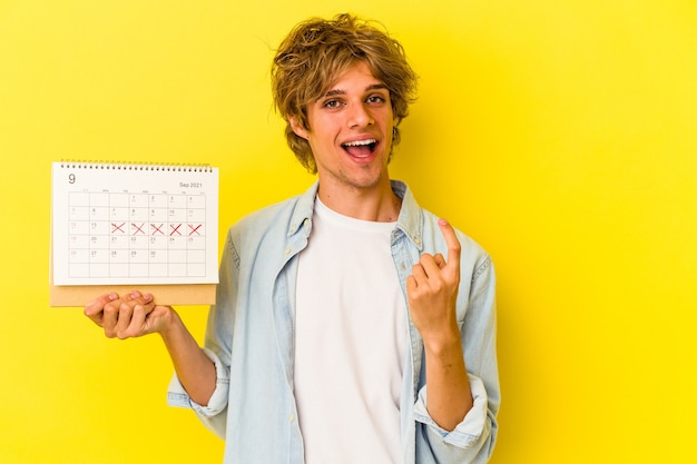 Jeune homme de race blanche avec du maquillage tenant un calendrier isolé sur fond jaune pointant le doigt vers vous comme s'il vous invitait à vous rapprocher.
