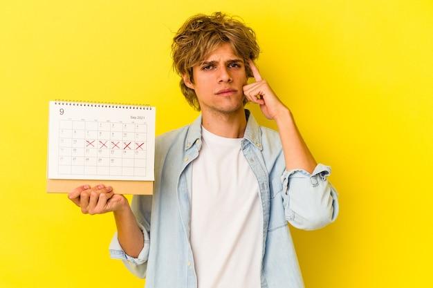 Jeune homme de race blanche avec du maquillage tenant un calendrier isolé sur fond jaune pointant le temple avec le doigt, pensant, concentré sur une tâche.