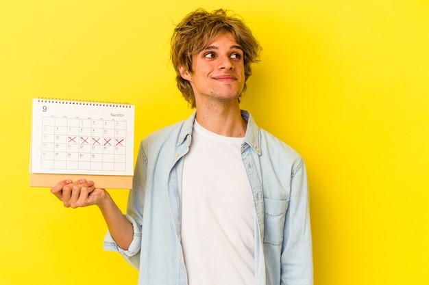 Jeune homme de race blanche avec du maquillage tenant un calendrier isolé sur fond jaune rêvant d'atteindre des objectifs et des buts
