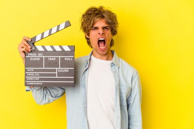 Jeune homme de race blanche avec du maquillage tenant un clap isolé sur fond jaune criant très en colère et agressif.