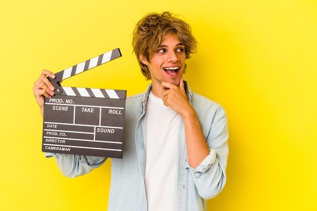 Jeune homme de race blanche avec du maquillage tenant un clap isolé sur fond jaune détendu en pensant à quelque chose en regardant un espace de copie.