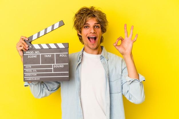 Jeune homme de race blanche avec du maquillage tenant un clap isolé sur fond jaune joyeux et confiant montrant un geste ok.