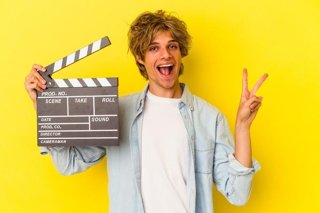 Jeune homme de race blanche avec du maquillage tenant un clap isolé sur fond jaune joyeux et insouciant montrant un symbole de paix avec les doigts.