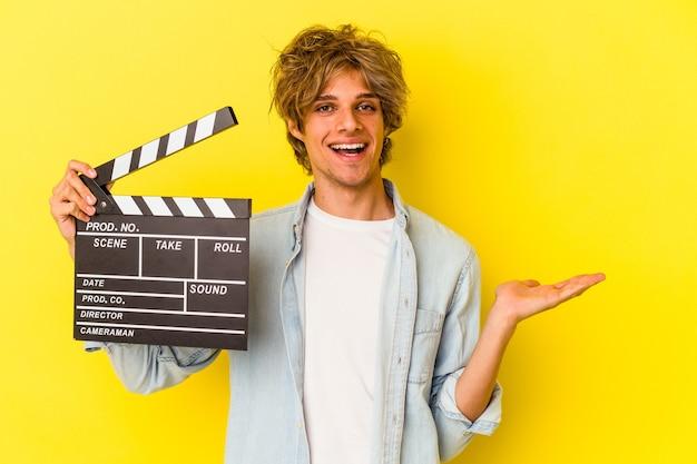 Jeune homme de race blanche avec du maquillage tenant un clap isolé sur fond jaune montrant un espace de copie sur une paume et tenant une autre main sur la taille.