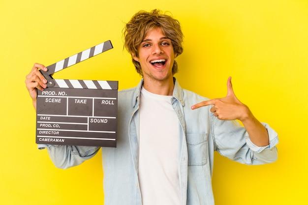 Jeune homme de race blanche avec du maquillage tenant un clap isolé sur fond jaune personne pointant à la main vers un espace de copie de chemise, fier et confiant