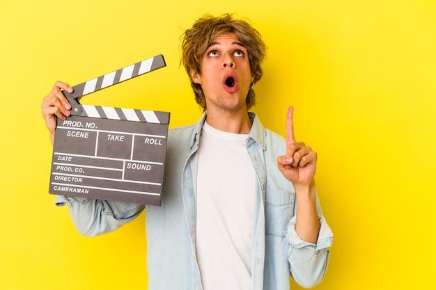 Jeune homme de race blanche avec du maquillage tenant un clap isolé sur fond jaune pointant vers le haut avec la bouche ouverte.