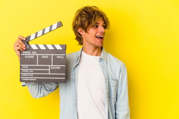 Jeune homme de race blanche avec du maquillage tenant un clap isolé sur fond jaune regarde de côté souriant, joyeux et agréable.