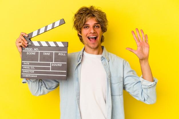 Jeune homme de race blanche avec du maquillage tenant un clap isolé sur fond jaune souriant joyeux montrant le numéro cinq avec les doigts.
