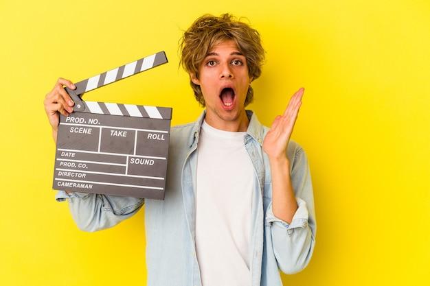 Jeune homme de race blanche avec du maquillage tenant un clap isolé sur fond jaune surpris et choqué.