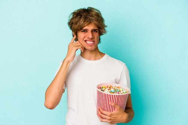 Jeune homme de race blanche avec du maquillage tenant du pop-corn isolé sur fond bleu couvrant les oreilles avec les mains.