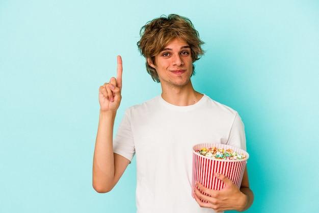 Jeune homme de race blanche avec du maquillage tenant du pop-corn isolé sur fond bleu montrant le numéro un avec le doigt.