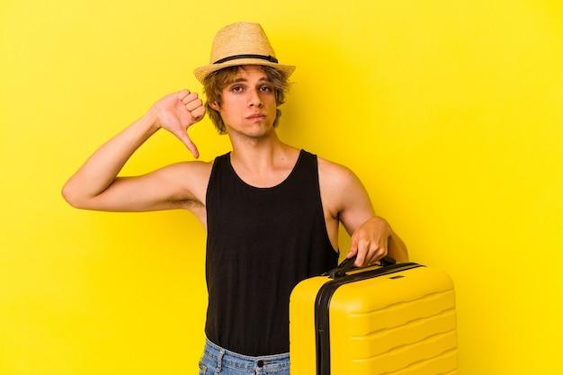 Jeune homme de race blanche avec du maquillage va voyager isolé sur fond jaune montrant un geste d'aversion, les pouces vers le bas. notion de désaccord.