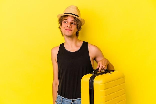 Jeune homme de race blanche avec du maquillage va voyager isolé sur fond jaune rêvant d'atteindre des objectifs et des buts