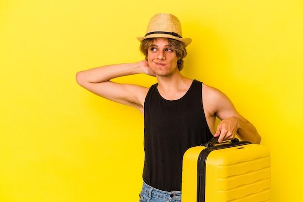 Jeune homme de race blanche avec du maquillage va voyager isolé sur fond jaune touchant l'arrière de la tête, pensant et faisant un choix.