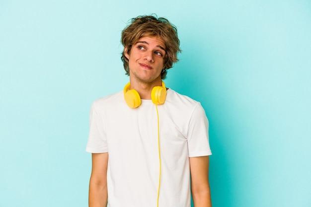Jeune homme de race blanche écoutant de la musique isolée sur fond bleu rêvant d'atteindre des objectifs et des objectifs