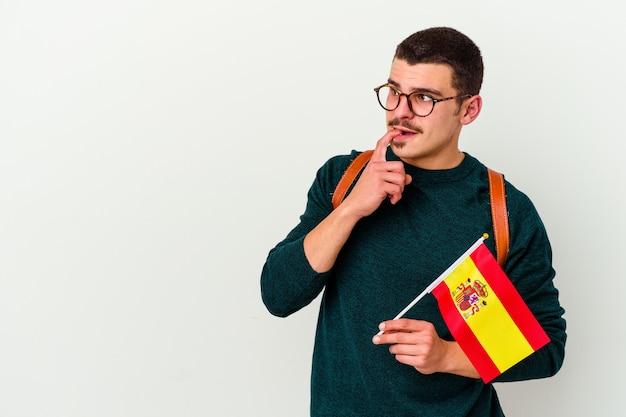 Jeune homme de race blanche étudie l'anglais sur blanc en pensant détendu à quelque chose en regardant un espace de copie.