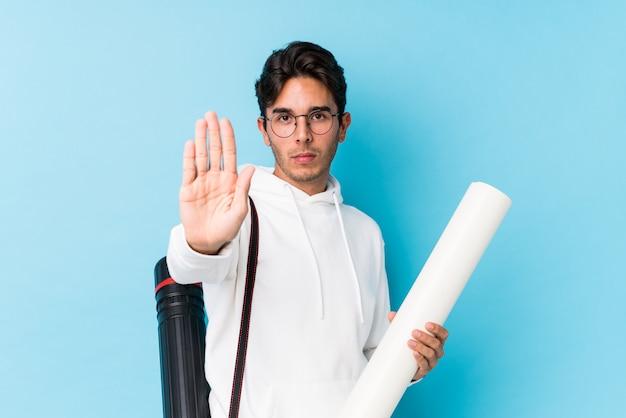 Jeune homme de race blanche étudie l'architecture debout avec la main tendue montrant le panneau d'arrêt