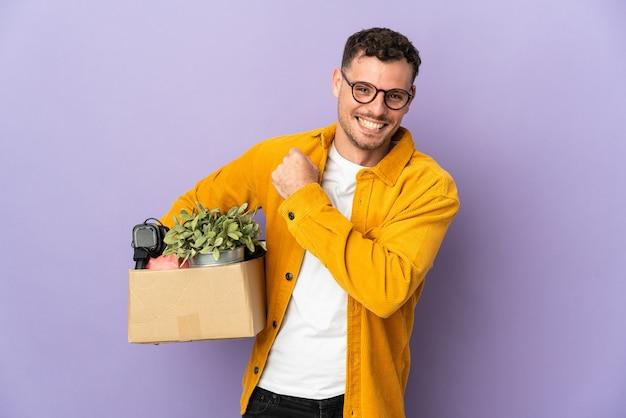 Jeune homme de race blanche faire un mouvement tout en ramassant une boîte pleine de choses isolées sur fond violet célébrant une victoire