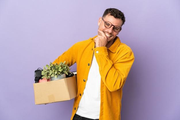 Jeune homme de race blanche faire un mouvement tout en ramassant une boîte pleine de choses isolées