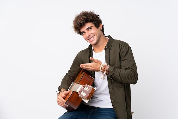 Jeune homme de race blanche avec guitare sur mur blanc isolé, tendant les mains sur le côté pour inviter à venir