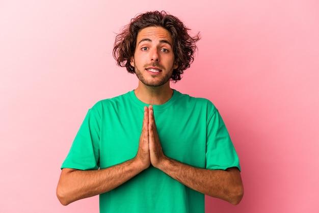 Jeune homme de race blanche isolé sur bakcground rose tenant la main dans la prière près de la bouche, se sent confiant.