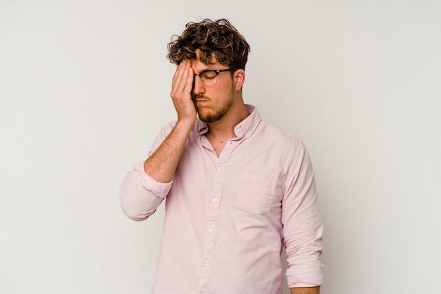 Jeune homme de race blanche isolé sur fond blanc ayant un mal de tête, touchant le devant du visage.