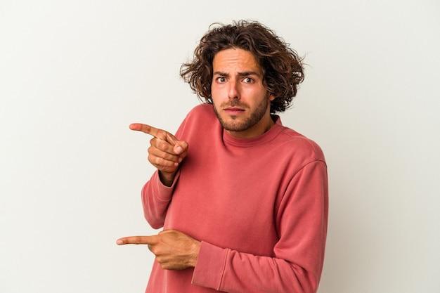 Jeune homme de race blanche isolé sur fond blanc choqué pointant avec l'index vers un espace de copie.