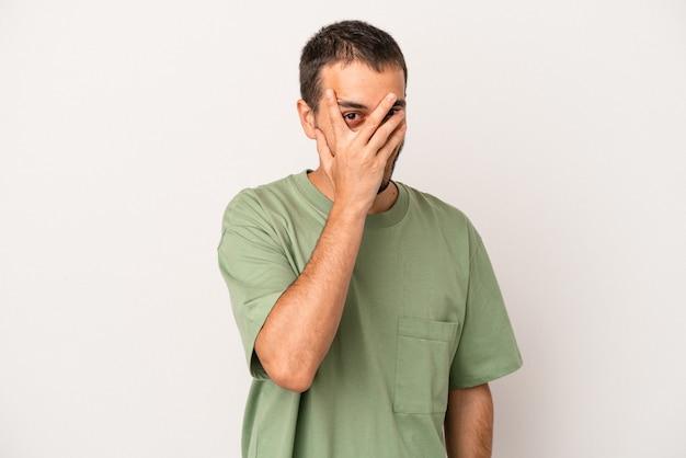 Jeune homme de race blanche isolé sur fond blanc clignote à la caméra à travers les doigts, embarrassé couvrant le visage.