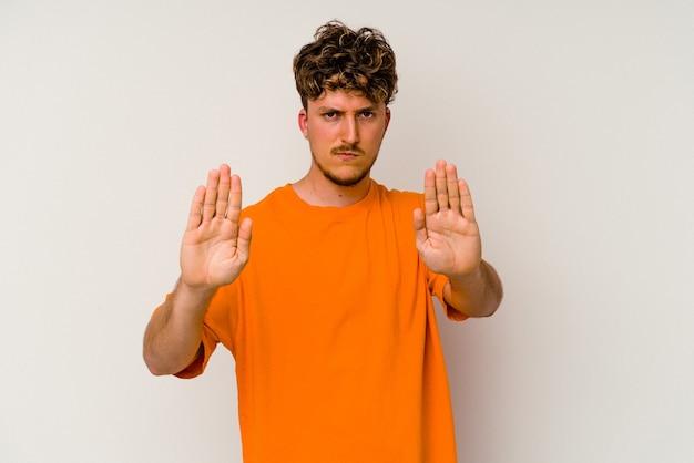 Jeune homme de race blanche isolé sur fond blanc debout avec la main tendue montrant un panneau d'arrêt, vous empêchant.