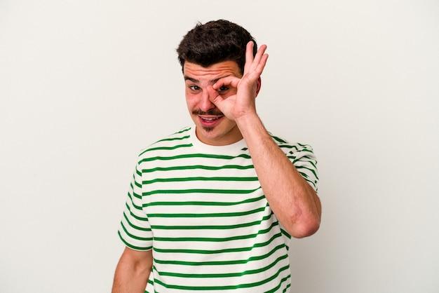Jeune homme de race blanche isolé sur fond blanc excité en gardant le geste ok sur les yeux.