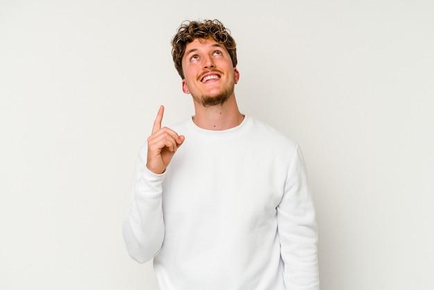 Jeune homme de race blanche isolé sur fond blanc indique avec les deux doigts antérieurs montrant un espace vide.