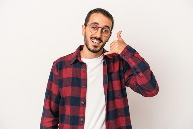 Jeune homme de race blanche isolé sur fond blanc montrant un geste d'appel de téléphone portable avec les doigts.