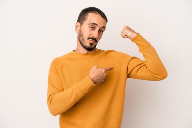 Jeune homme de race blanche isolé sur fond blanc montrant un geste de force avec les bras, symbole du pouvoir féminin