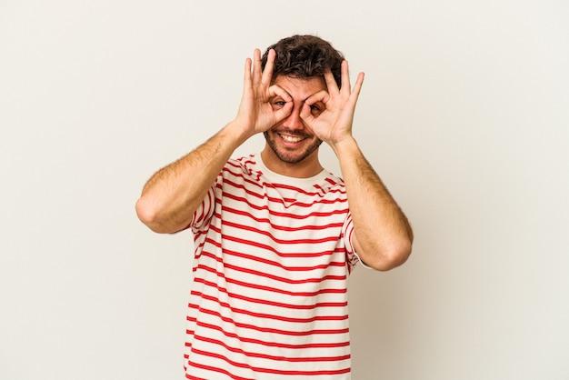 Jeune homme de race blanche isolé sur fond blanc montrant un signe d'accord sur les yeux