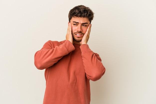 Jeune homme de race blanche isolé sur fond blanc pleurnicher et pleurer inconsolablement.