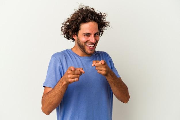 Jeune homme de race blanche isolé sur fond blanc pointant vers l'avant avec les doigts.