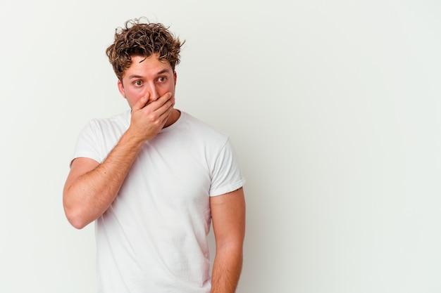 Jeune homme de race blanche isolé sur fond blanc réfléchi à la recherche d'un espace de copie couvrant la bouche avec la main.