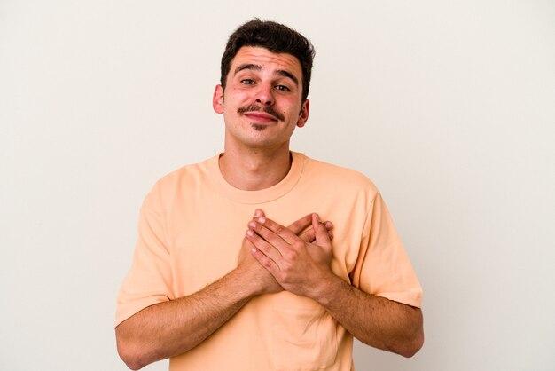 Jeune homme de race blanche isolé sur fond blanc en riant en gardant les mains sur le cœur, concept de bonheur.