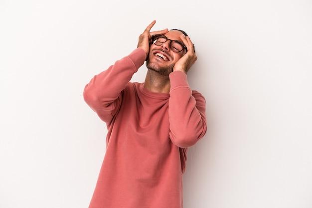 Jeune homme de race blanche isolé sur fond blanc rit joyeusement en gardant les mains sur la tête. notion de bonheur.