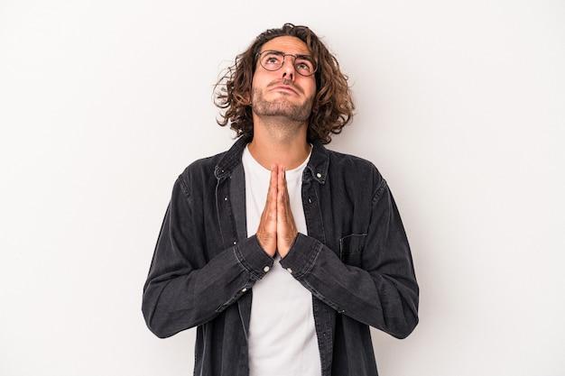 Jeune homme de race blanche isolé sur fond blanc se tenant la main dans la prière près de la bouche, se sent confiant.