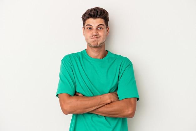 Jeune homme de race blanche isolé sur fond blanc souffle les joues, a une expression fatiguée. concept d'expression faciale.