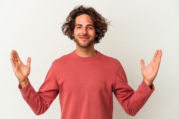 Jeune homme de race blanche isolé sur fond blanc tenant quelque chose de petit avec les index, souriant et confiant.