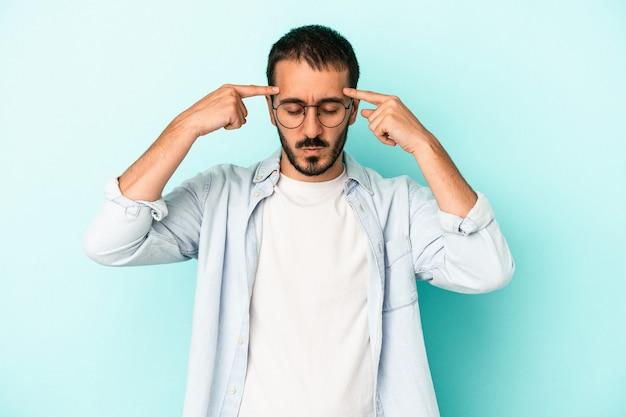 Jeune homme de race blanche isolé sur fond bleu concentré sur une tâche, gardant les index pointant la tête.