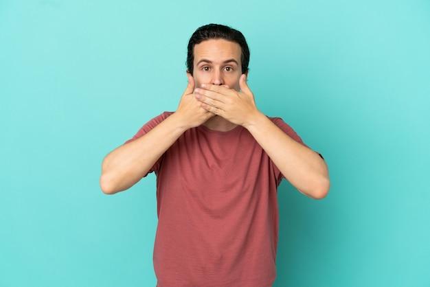 Jeune homme de race blanche isolé sur fond bleu couvrant la bouche avec les mains