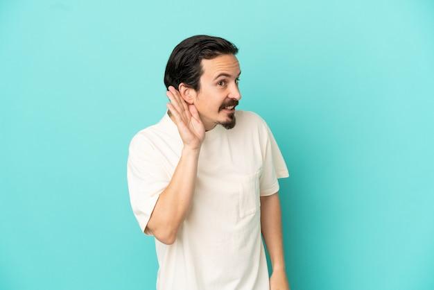 Jeune homme de race blanche isolé sur fond bleu écoutant quelque chose en mettant la main sur l'oreille