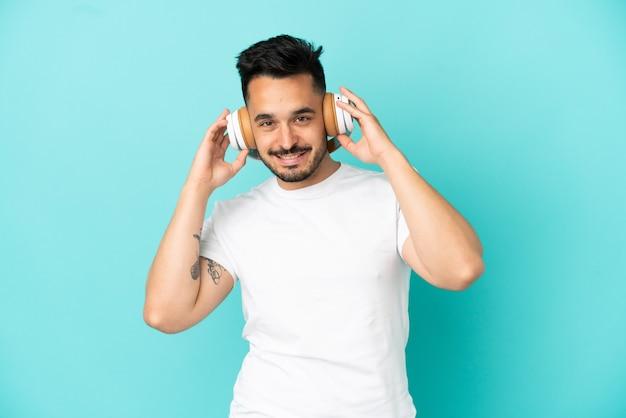 Jeune homme de race blanche isolé sur fond bleu, écouter de la musique