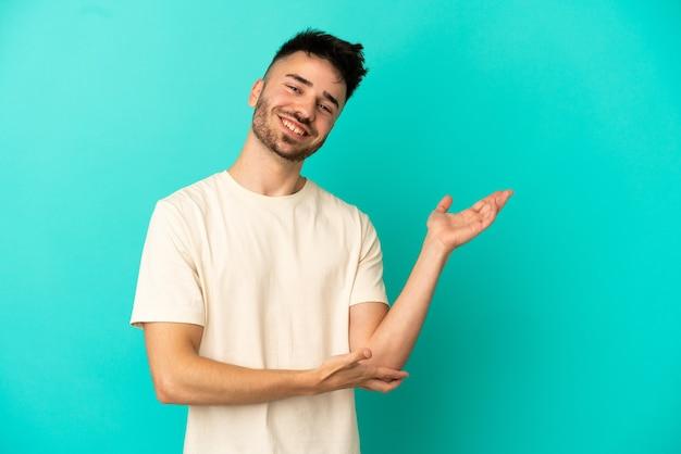 Jeune homme de race blanche isolé sur fond bleu étendant les mains sur le côté pour inviter à venir