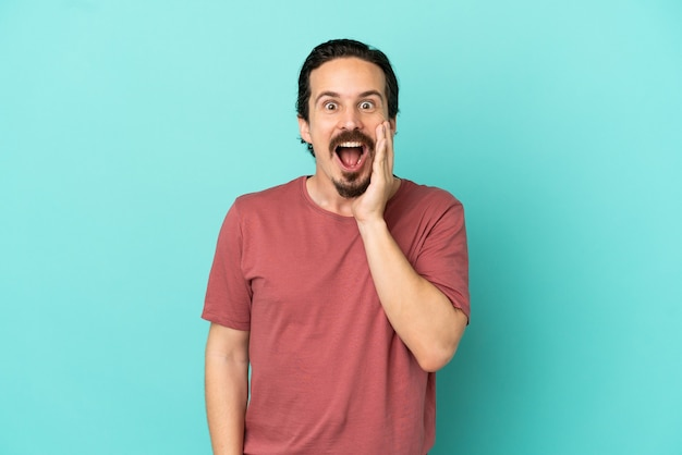 Jeune homme de race blanche isolé sur fond bleu avec une expression faciale surprise et choquée